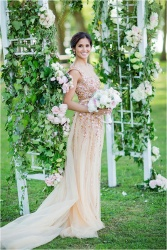 bride-in-gold-wedding-dress-by-floral-arch