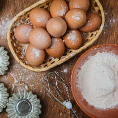 Baking cake in rural kitchen - dough recipe ingredients (eggs, flour, sugar) on vintage wooden table from above.